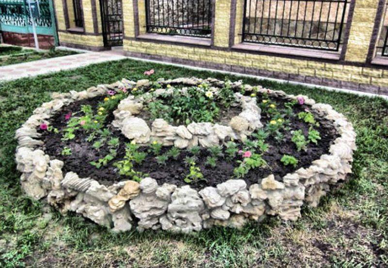 Кругла клумба з каменю для квітів